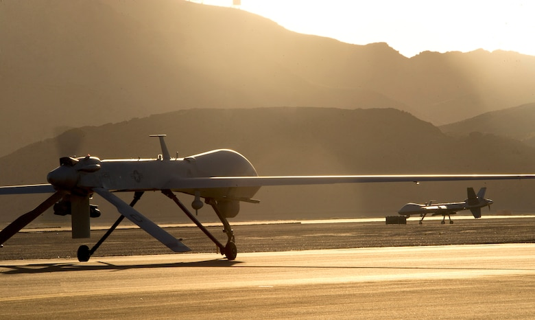 An MQ-1 Predator and MQ-9 Reaper taxi to the runway in preparation for take-off June 13, 2014, at Creech Air Force Base, Nev.. The aircraft are flown under the 432nd Wing, which trains pilots, sensor operators, and other remotely piloted aircraft crewmembers, and conducts combat surveillance and attack operations worldwide. (U.S. Air Force photo/Airman 1st Class Christian Clausen)