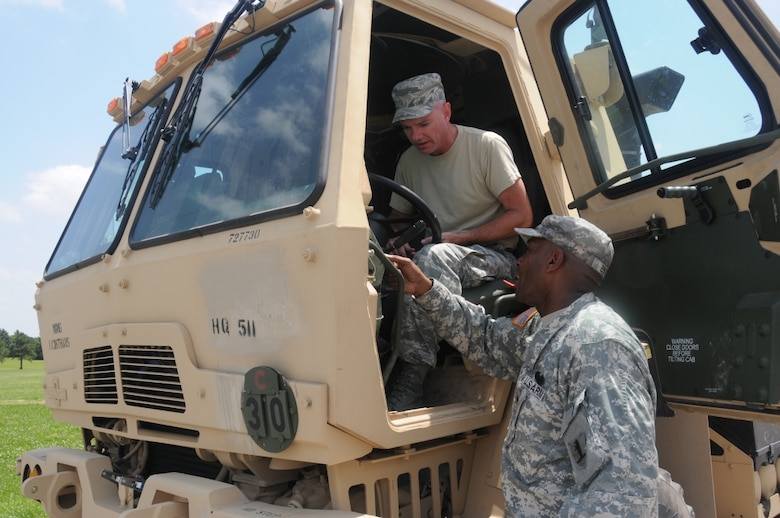 Missouri Air National Guard Tech. Sgt. Jarred Anderson, 131st Bomb Wing Maintenance Group, and Missouri Army National Guard Staff Sgt. John Byrd, 3rd squadron leader, 2nd platoon, 1138th Transportation Company, discuss the M1088 Troop Transport Vehicle during state emergency duty training at Camp Clark in Nevada, Missouri, on June 17, 2014. Missouri Citizen Airmen and Soldiers worked side by side during the week-long annual training exercise that included driving, map reading, an obstacle course and leadership course. (U.S. Air National Guard photo by Senior Airman Nathan Dampf/RELEASED)