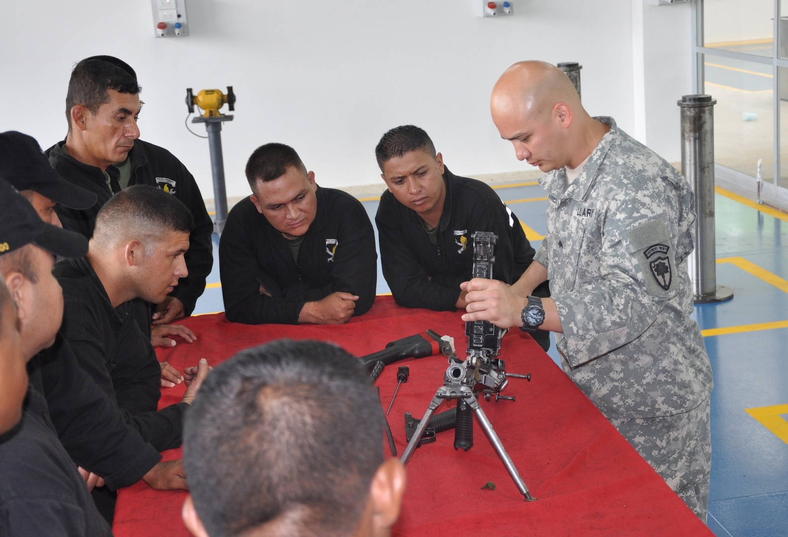 U.S. Army Sgt. Daniel Garcia-Benedetti, a small arms repairman in the 742nd Support Maintenance Company, South Carolina National Guard, teaches Colombian army maintenance workers how to troubleshoot malfunctions and break down an M240 machine gun, June 2014.