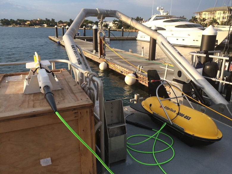 The large yellow capsule is the Edgetech 2000DS, which houses the side scan sonar and sub-bottom profiler. The side scan sonar sees the surface of the ocean floor and the sub-bottom profiler detects features just beneath the surface. Attached to this equipment via the green cable is the magnetometer, which is like a metal detector that picks up ferrous materials above and below the surface of the ocean floor, particularly ship hulls, ship elements, fittings, cannons, anchors and more.