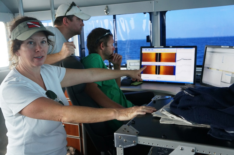 Archaeologist Wendy Weaver (left) and Florida II crew members Matt Staley (center) and Chad Harralson (right) review data in real time as they tow the equipment in transects over a pre-selected area. The left monitor shows the sub-bottom profiler with results in orange and the side scan sonar on the right. The magnetometer readings are visible on the far right monitor.