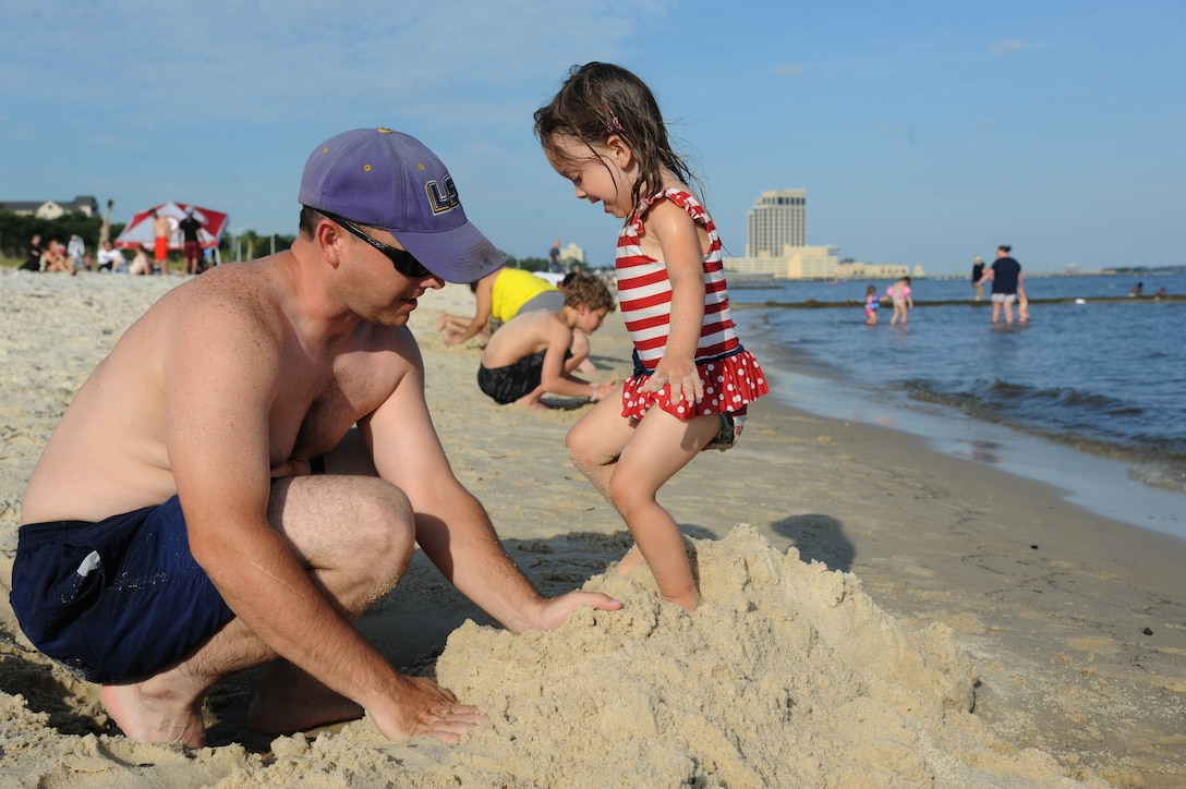 Tech. Sgt. Kyle Pourciau, Keesler firefighter, and his daughter collapse a sand castle during Keesler's 4th of July Beach Bash on Biloxi Beach, Miss.  The event included contests, music, games, food and fireworks.  (U.S. Air Force photo by Kemberly Groue)