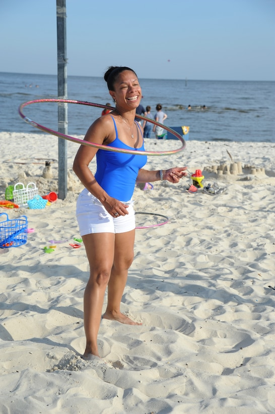 Master Sgt. Nicole Dismute, 81st Medical Support Squadron, spins a hula-hoop around her neck during Keesler's 4th of July Beach Bash on Biloxi Beach, Miss.  The event included contests, music, games, food and fireworks.  (U.S. Air Force photo by Kemberly Groue)