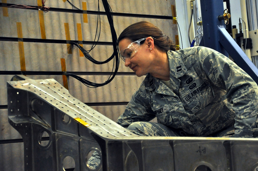 "Capt. Allison Dempsey, Air Force Research Laboratory Aerospace Systems Directorate deputy branch chief, Wright-Patterson Air Force Base, Ohio, prepares for an experiment using the Structural Health Monitoring Test Bed. The SHM Test Bed enables AFRL researchers to investigate the performance of emerging instrumentation technologies for sensing fatigue cracking and strain in aircraft structures. In this experiment, a beam-like structure is being used as an analog for real aircraft structures. New instrumentation technologies will enable improved characterization of damage state and usage in aircraft structures. ""The technology options AFRL provides give our warfighters an advantage on the battlefields of today and tomorrow,"" said AFRL commander Maj. Gen. Thomas Masiello. ""Those options help ensure we are on the right side of an unfair fight against America's adversaries, and it's our mission to keep it that way."" (Air Force photo by Michele Eaton)"