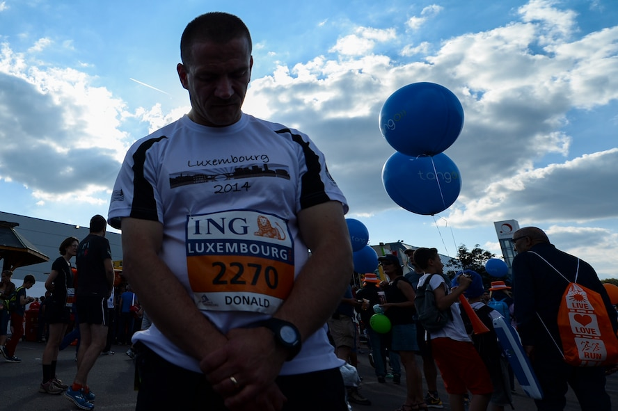 U.S. Air Force Master Sgt. Donald Stichter, 52nd Equipment Maintenance Squadron NCO in charge of munitions inspection, from Lakewood, Colo., prays right before running in the ING Luxembourg Night Marathon May 31, 2014, in Luxembourg. Comprehensive Airman Fitness is a holistic approach to develop over-arching Airman fitness and resilience. Its four pillars include physical, mental, spiritual and social aspects. (U.S. Air Force photo by Senior Airman Rusty Frank/Released)