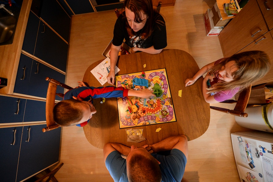 U.S. Air Force Master Sgt. Donald Stichter, 52nd Equipment Maintenance Squadron NCO in charge of munitions inspection from Lakewood, Colo., plays a board game with his family May 5, 2014 at his house in Malbergwelch, Germany. Stichter credits his family's love and support to his success while training and competing in his first marathon. (U.S. Air Force photo by Senior Airman Rusty Frank/Released)