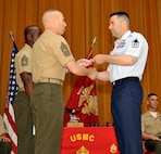 Master Sgt. Joseph P. Connolly, 731st Air Mobility Squadron passenger services section chief, receives his U.S. Marine Corps Staff NCO Academy diploma from USMC Sgt. Maj. Jerry L. Bates, Headquarters and Service Battalion, Marine Corps Base, Camp Smedly D. Butler senior enlisted advisor, during Class 14-4's graduation at Camp Hansen, Japan, June 13, 2014. Connolly graduated from the advanced course that provides Marines and specially selected Airmen with the knowledge and skills necessary to assume leadership roles of greater responsibilty. (U.S. Air Force photo/Naoto Anazawa)