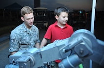 Staff Sgt. Andrew Trelly, 51st Civil Engineer Squadron explosive ordnance disposal team leader, helps Ty Mathis, 7, operate an EOD robot during Liberty Fest at Osan Air Base, Republic of Korea, July 4, 2014. Several units hosted demonstrations throughout the night which ended with a fireworks display. (U.S. Air Force photo/Airman 1st Class Ashley J. Thum)