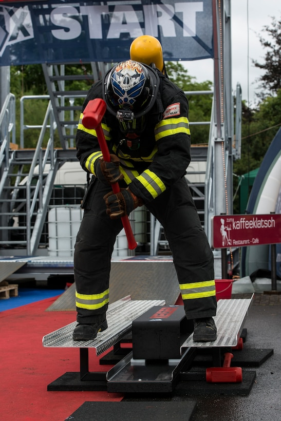 Tech. Sgt. James Hickom hammers the Keiser force machine during the first Mosel Firefighter Combat Challenge July 5, 2014, in Ediger-Eller, Germany. The Keiser force machine simulates hammering a hole into a burning building. Hickom is the U.S. Air Forces in Europe and Air Forces Africa's 435th Construction and Training Squadron fire academy NCO in charge at Ramstein Air Base, Germany. (U.S. Air Force photo/Staff Sgt. Christopher Ruano)