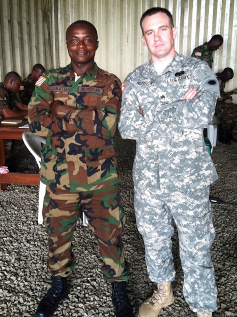 Michigan National Guard Sgt. Matthew Robinson and Liberian Armed Forces soldier Pvt. 1st Class Musa Jabateh pose for a picture during a training exercise at Edward B. Kesselly Barracks in Monrovia, Liberia, June 12, 2014.