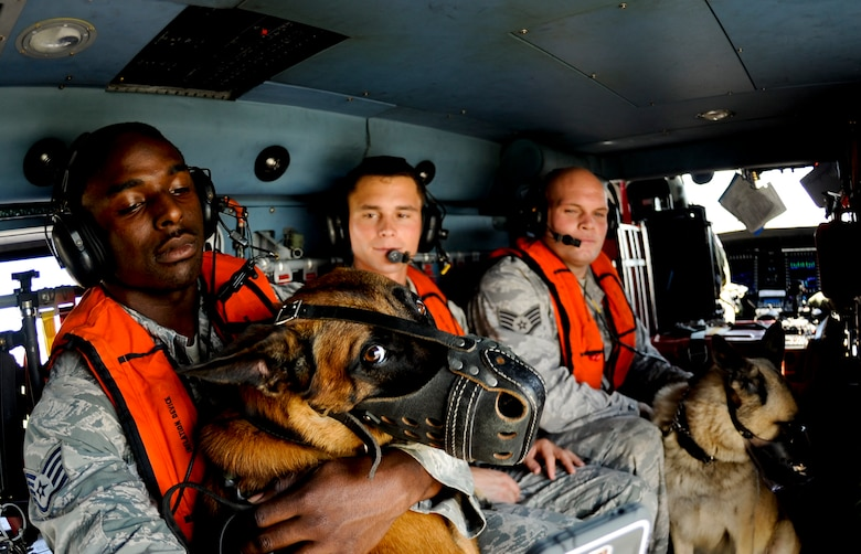 Staff Sgt. Winston Campbell comforts his military working dog, Lleonard, during a training helicopter ride with the U.S. Coast Guard June 30, 2014, at Air Station Clearwater, Fla. This was Lleonard's first time being exposed to the noise of a helicopter along with the high altitude. Campbell is a 6th Security Forces Squadron MWD handler. (U.S. Air Force photo/Senior Airman Melanie Bulow-Gonterman)