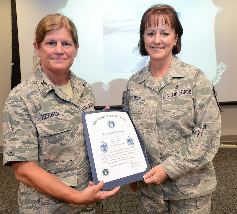 U.S. Air Force Col. Muriel Herman, 116th Medical Group (MDG) commander, Georgia Air National Guard, presents Chief Master Sgt. Cynthia Haines a certificate of promotion to the rank of Chief Master Sgt., Robins Air Force Base, Ga., June 21, 2014. Haines became the first female to be promoted to Chief Master Sgt. in the history of the 116th MDG. The 116th MDG is the medical arm of the 116th Air Control Wing.  (U.S. Air National Guard photo by Master Sgt. Roger Parsons/Released)