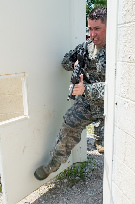 U.S Air Force Staff Sgt. Sean Reed, a member of the 116th Security Forces Squadron, Georgia Air National Guard, breaches a building during training at the Catoosa Training Site, Tunnel Hill, Ga., June 27, 2014. The squadron deployed to the Catoosa Training Site for annual training where they received extensive classroom and hands-on training to hone their skills on various firearms such as the M4 carbine, M203 grenade launcher and M240 and M249 machine guns as well as training in various security operations performed by Air Force security forces personnel. (U.S. Air National Guard photo by Master Sgt. Roger Parsons/Released)