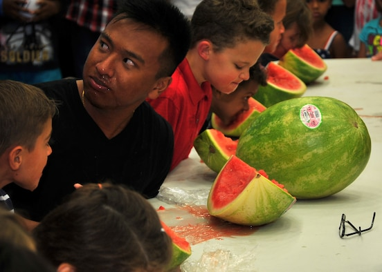 Members of Team Andersen participate in a watermelon eating contest at the Freedom Fest event July 4, 2014, on Andersen Air Force Base, Guam. Wallyball and pingpong tournaments, face painting, and watermelon eating contests were some of the events held during Freedom Fest at the Coral Reef Fitness Center in celebration of Independence Day. (U.S. Air Force photo by Staff Sgt. Melissa B. White/Released)