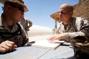 Marine Corps Cpl. Michael Kean, right, discusses the instructions for the day with a fellow Marine during a desert training exercise, June 16, 2014. U.S. Marine Corps photo by Sgt. Adwin Esters