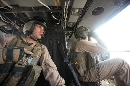 Staff Sgt. Jonathan Lee, left, and Staff Sgt. Kenneth Morris, both crew chiefs with Marine Light Attack Helicopter Squadron 467, watch for any suspicious activity on the ground during a mission in Helmand province, Afghanistan, July 3, 2014. Marine Light Attack Helicopter Squadron 467 was established five years ago aboard Marine Corps Air Station Cherry Point, N.C., and is on their first combat deployment as a squadron. The Marines of HMLA-467 will be the last Marines to conduct close-air support operations in Afghanistan in support of Operation Enduring Freedom. (U.S. Marine Corps Photo By: Sgt. Frances Johnson/Released)