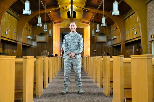 Captain Matthew Spencer, 325th Fighter Wing chaplain, stands between the pews in Chapel 2 at Tyndall Air Force Base July 3. 2014. Spencer was a prior enlisted member of security forces before he commissioned as an officer and became a chaplain in the Air Force Reserve. (U.S. Air Force photo by 2nd Lt. Christopher Bowyer-Meeder)
