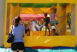 Children bounce in the moon bounce as their parents watch during the Independence Day Celebration on Lejeune Field July 4, 2014. The celebration started at 3 p.m. and went until 9:30 p.m.