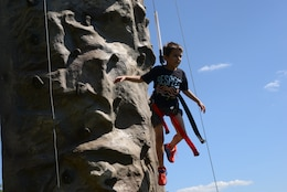 Caleb, 7, coasts back to the ground after reaching the top of the rock wall during the Independence Day Celebration on Lejeune Field July 4, 2014. The rock wall was one of many activities available for entertainment as patrons waited for the fireworks to begin.