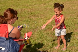 Alayjah, 2, screeches in excitement as Nancy Bentley, her mother, sends bubbles her way during the Independence Day celebration on Lejeune Field July 14, 2014.
