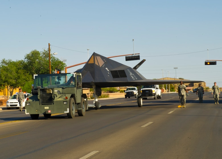 Members of Team Holloman walk along side the F-117 Nighthawk down First Street at Holloman Air Force Base, N.M., June 28. The F-117 has been on static display in Holloman's Heritage Airpark since its retirement in 2008. Due to sun and inclement weather damage, the 49th Maintenance Squadron removed and towed the aircraft to begin the restoration process. The aircraft received structural maintenance, and a fresh paint job before it was returned for display in Heritage Airpark. (U.S. Air Force photo by Airman 1st Class Leah Ferrante/Released)