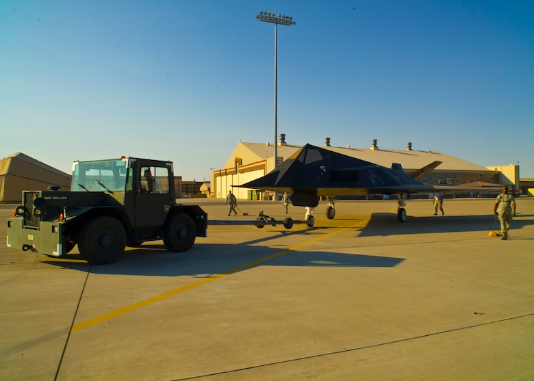 Members of Team Holloman start the towing process of the F-117 Nighthawk back to Heritage Airpark at Holloman Air Force Base, N.M., June 28. The F-117 has been on static display in Holloman's Heritage Airpark since its retirement in 2008. Due to sun and inclement weather damage, the 49th Maintenance Squadron removed and towed the aircraft to begin the restoration process. The aircraft received structural maintenance, and a fresh paint job before it was returned for display in Heritage Airpark. (U.S. Air Force photo by Airman 1st Class Leah Ferrante/Released)
