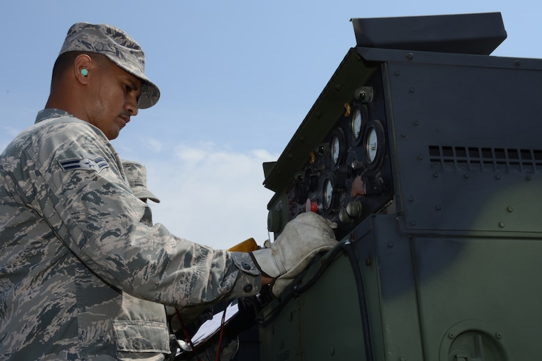 Airman 1st Class Erin Cruz, an aerospace ground equipment technician from the 103rd Air Control Squadron, performs maintenance on one of the generators that supply power to the unit's tactical site while deployed to the National Guard Training Center, Sea Girt, N.J., June 10.  The unit operated in field conditions using generated power to enable operators to command and control simulated military aircraft from the field. (U.S. Air National Guard photo by Senior Airman Emmanuel Santiago)