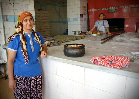 A woman poses in front of a stone pot at a local bakery July 9, 2014, near Incirlik Air Base, Turkey. Many Muslims in Turkey participate in fasting for Ramazan, during this time they will not eat or drink during daylight hours. Bakeries offer specialty breads during Ramazan after the fasting period. (U.S. Air Force photo by Staff Sgt. Veronica Pierce/Released)