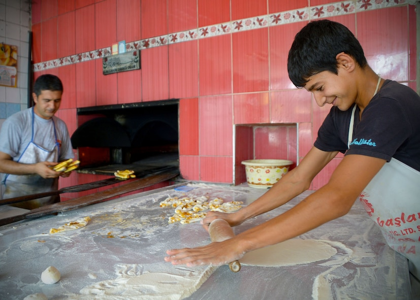 At a local bakery in a village near Incirlik Air Base, Turkey, a boy helps prepare bread for the breaking of fast during Ramazan July 9, 2014. During this month, Muslims around world fast. At night families and friends gather for dinner to break the fast.  Many locals go to bakeries to buy a specialty breads baked during Ramazan. (U.S. Air Force photo by Staff Sgt. Veronica Pierce/Released)