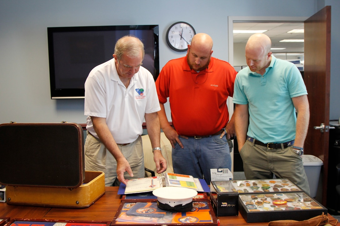 The Charleston District has nine Eagle Scouts in our approximately 250 employees. Each of these Eagle Scouts has a different story about their experience. Here, Joe Moran, Caleb Brewer and Sean McBride look at Moran's collection of Boy Scouts memorabilia.