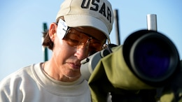 Col. Denise Loring checks a competitor's shot through a scope during the 53rd Annual Interservice Rifle Championship at Marine Corps Base Quantico, Virginia, July 7, 2014. The best shooters from all services are selected and earn their way to participate in competitions. Loring is a reservist officer with the Office of the Secretary of Defense.