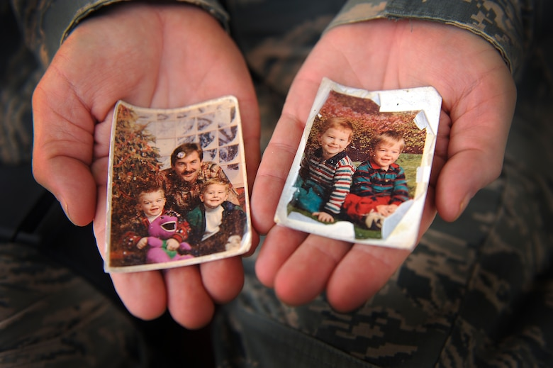 Staff Sgt. Ronald Ball displays photos of his sons that he keeps in his wallet June 25, 2014, at an undisclosed location in Southwest Asia. The photos were taken just before the murder of his wife in 1995. (U.S. Air Force photo/Tech. Sgt. Russ Scalf)