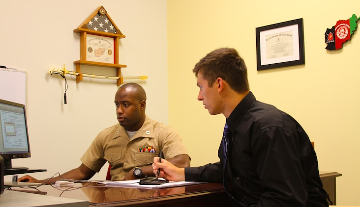 U.S. Marine Corps Capt. Devin Claridy, (left), guides Jamie Gastrich, an officer candidate and a Richmond, Va. native, through his enlistment contract at Officer Selection Station Norfolk in Norfolk, Va., July 7, 2014. Gastrich, a junior at Old Dominion University, became the first candidate to sign an enlistment contract at Recruiting Station Richmond's newest officer selection station. (U.S. Marine Corps photo by Cpl. Aaron Diamant/Released)