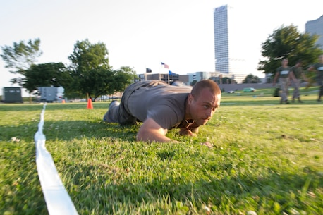 Applicant Nolan McShane executes a high crawl during the maneuver under fire portion of the Combat Fitness Test at Veterans Park in Milwaukee, Wis., July 10, 2014.  Officer Selection Station Milwaukee conducted a Combat Fitness Test to help prepare their officer candidates and applicants for Officer Candidates School.