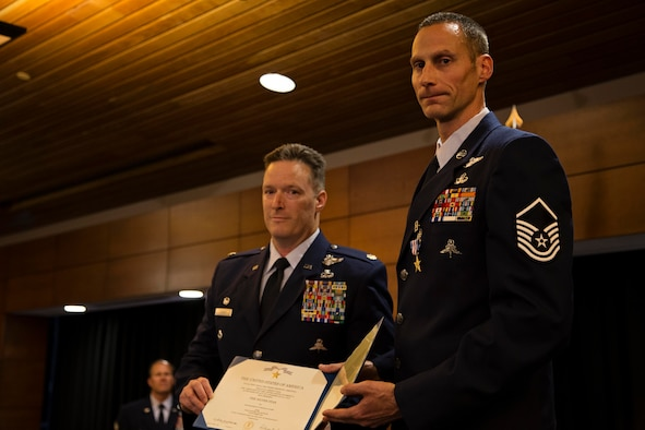 Master Sgt. Roger Sparks (right), and Maj. Joseph Conroy, both with the 212th Rescue Squadron, Alaska Air National Guard, hold an award citation during a ceremony on Joint Base Elmendorf-Richardson, July 11. Sparks was awarded the Silver Star, the nation's third-highest award for valor, for his role in a firefight with insurgents during Operation Bulldog Bite in Afghanistan's Watapur Valley on Nov. 14, 2010. His actions during the combat operation resulted in four American lives being saved and four casualties being returned to their families with honor and dignity. (U.S. Army National Guard photo by Sgt. Edward Eagerton/released)