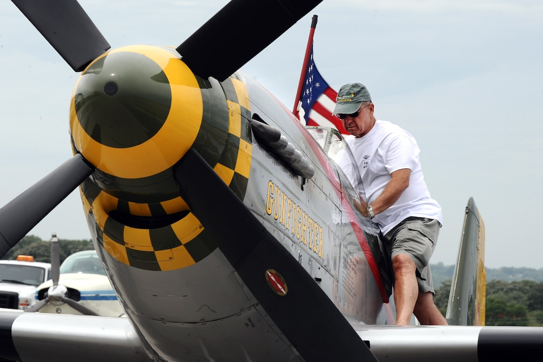 Larry Lumpkin, P-51 Gunfighter Mustang pilot, props up the American flag as he prepares the plane for a media photo shoot at the Council Bluffs Municipal Airport, Iowa on June 27. A commercial pilot for United Airlines, Lumpkin spends his free time chasing a Tora 101 replica Zero at air shows across the nation.  (U.S. Air Force photo by Josh Plueger/Released)