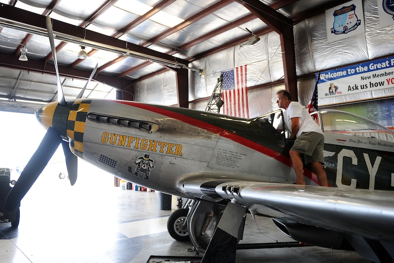 Larry Lumpkin, P-51 Gunfighter Mustang pilot, stands on the wing of the aircraft as he prepares to pull it from a hangar located at the Council Bluffs Municipal Airport, Iowa, on June 27. Lumpkin has amassed more than 700 hours in the in the Mustang cockpit performing an average of eight-to-ten air shows annually.  (U.S. Air Force photo by Josh Plueger/Released)