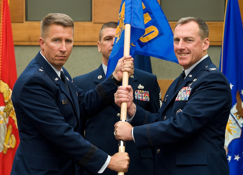 Brig. Gen. Patrick J. Doherty, Director of Air Force Services, Headquarters U.S. Air Force, Washington, D.C., presents the Air Force Mortuary Affairs Operations guidon to Col. Daniel F. Merry, the new AFMAO commander, during a change of command ceremony July 11, 2014 in the atrium of the Charles C. Carson Center for Mortuary Affairs, Dover Air Force Base, Del.  (U.S. Air Force photo/Roland Balik)