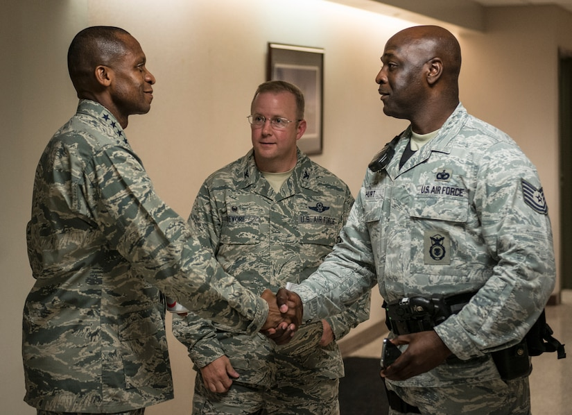 Gen. Darren McDew, Air Mobility Commander commander, coins Tech. Sgt. Dwayne Hurt, 628th Security Forces Squadron patroleman July 11, 2014, at Joint Base Charleston, S.C. McDew visited JB Charleston to get a firsthand look at how joint basing builds closer relationships and forges stronger ties between our sister services. (U.S. Air Force photo/Senior Airman Dennis Sloan)