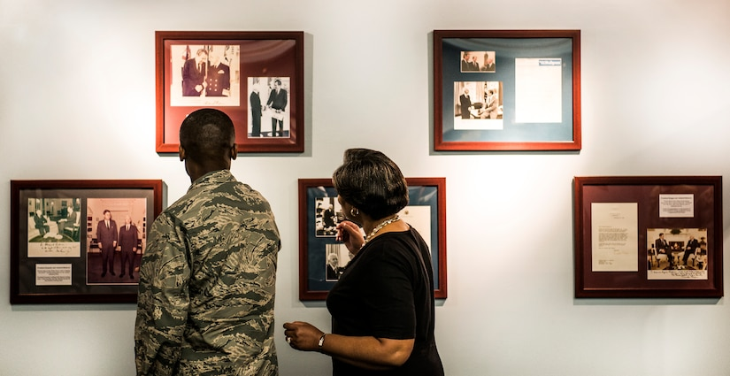 Gen. Darren McDew, Air Mobility Commander commander, and his wife, Evelyn, look at photos on the wall inside the Naval Nuclear Power Training Command building, July 10, 2014, at Joint Base Charleston, S.C. McDew visited JB Charleston to get a firsthand look at how joint basing builds closer relationships and forges stronger ties between our sister services. (U.S. Air Force photo/Senior Airman Dennis Sloan)