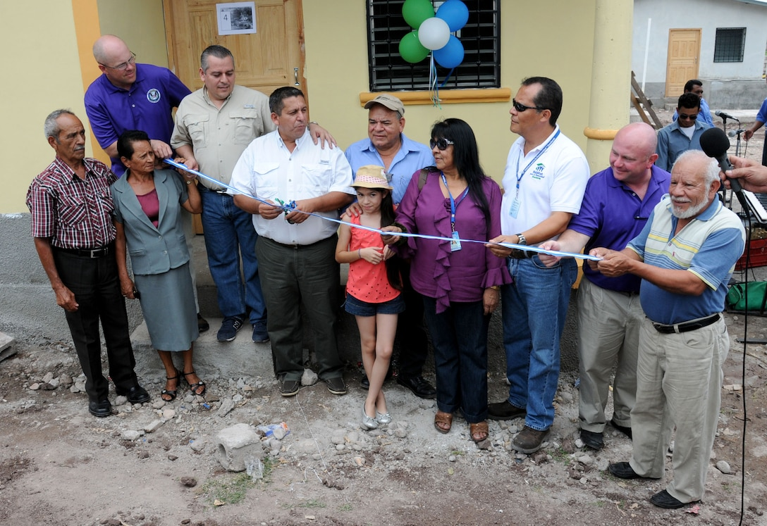 Joint Task Force-Bravo, Honduras Habitat for Humanity-Siguatepeque region, Municipality of Ajuterique officials and other volunteers cut the ribbon during a Habitat for Humanity house dedication in Ajuterique, Department of Comayagua, Honduras, July 5, 2014 where 18 local families received the keys to their new homes.  Volunteers from JTF-Bravo worked over 600 hours on Saturdays filling trenches, leveling ground and shoveling dirt at the Ajuterique Housing Project helping these Honduran families construct their homes.  (Photo by U. S. Air National Guard Capt. Steven Stubbs)