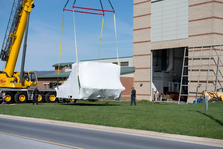 The main body of the C-5 flight simulator is hoisted away from the flight safety building by crane, April 17. The simulator was taken to Letterkenny Army Depot.(Air National Guard photo by Capt. Christopher Tusing)