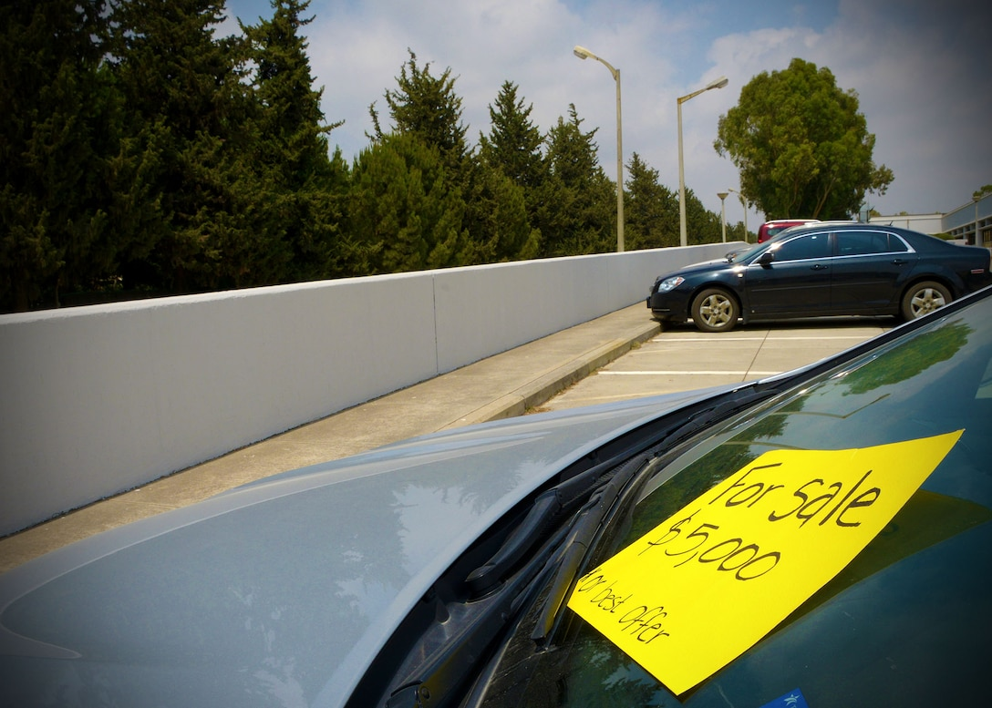 A vehicle sits in a parking lot with a 'for sale' sign on the windshield July 11, 2014, Incirlik Air Base, Turkey. Transferring a Privately Owned Vehicle from one U.S. member to another is a process that requires special documentation with command approval and coordination through the Turkish Customs Liaison Office. (U.S. Air Force photo by Staff Sgt. Veronica Pierce)