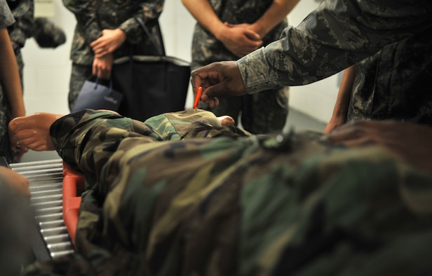 Tech. Sgt. Destin Huey, 51st Aerospace Medicine Squadron optometry technician and night shift alternate decontamination team chief for operational readiness exercises, simulates cutting off a mock chemical attack casualty's Mission Oriented Protective Posture gear during a tour of the 51st Medical Group at Osan Air Base, Republic of Korea, July 11, 2014. Students from the Republic of Korea Aeromedical Center Primary Flight Nurse Course visited the decontamination area and emergency room after receiving a briefing about the 51st MDG's mission and capabilities. (U.S. Air Force photo/Airman 1st Class Ashley J. Thum)