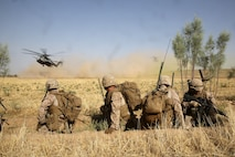 Marines with Bravo Company, 1st Battalion, 7th Marine Regiment, watch as CH-53E Super Stallion helicopters land in a field during a mission in Helmand province, Afghanistan, July 5, 2014. The company operated in Gereshk for three days and was involved in numerous kinetic engagements with Taliban insurgents.