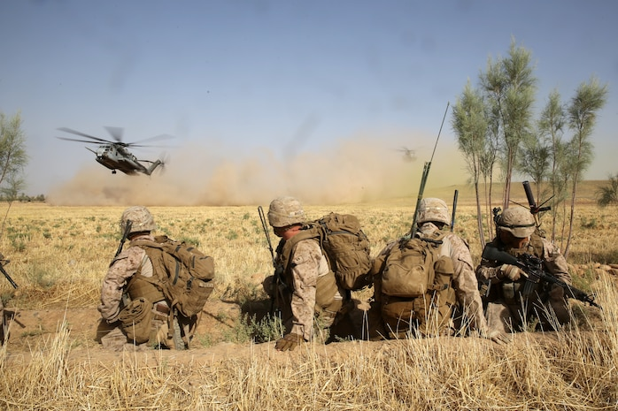 Marines with Bravo Company, 1st Battalion, 7th Marine Regiment, watch as CH-53E Super Stallion helicopters land in a field during a mission in Helmand province, Afghanistan, July 5, 2014. The company operated in Gereshk for three days and was involved in numerous kinetic engagements with Taliban insurgents. (U.S. Marine Corps photo by Cpl. Joseph Scanlan / released)