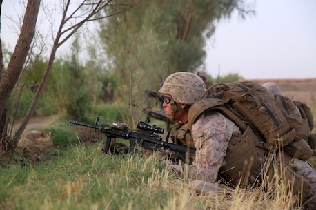 Petty Officer 3rd Class Heston Johnson, corpsman, Bravo Company, 1st Battalion, 7th Marine Regiment, provides security during a mission in Helmand province, Afghanistan, July 4, 2014. Johnson, a native of Athena, Ore., and the company operated in Gereshk for three days and were involved in numerous kinetic engagements with Taliban insurgents. (U.S. Marine Corps photo by Cpl. Joseph Scanlan / released)