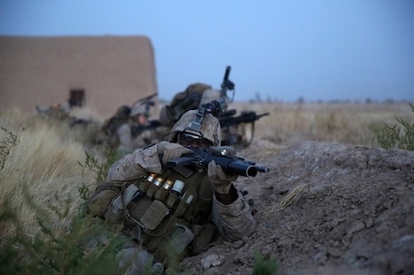 Corporal Deshaun Jackson, rifleman, Bravo Company, 1st Battalion, 7th Marine Regiment, takes cover behind a berm during a firefight in Helmand province, Afghanistan, July 6, 2014. Jackson, a native of Chicago, and the company operated in Gereshk for three days and were involved in numerous kinetic engagements with Taliban insurgents. (U.S. Marine Corps photo by Cpl. Joseph Scanlan / released)