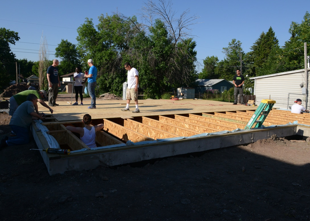 A dozen Malmstrom Air Force Base Airmen work together to lay plywood down for the subfloor of unit 31, a Habitat for Humanity home in Great Falls, Mont., July 12. Approximately 25 families are on the waiting list to receive a home, which takes nine months to build. (U.S. Air Force photo/Senior Airman Katrina Heikkinen)