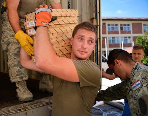 U.S. Air Force Airmen from the 133rd and 148th Civil Engineering Squadron and 219th Red Horse Squadron in partnership with the Croatian Army unload school supplies at an elementary school in Ogulin, Croatia, July 3, 2014. The school supplies were donated from school closures in Germany, base closures at U.S. Army installations in Europe and other various locations. (U.S. Air National Guard photo by Staff Sgt. Austen Adriaens/Released)